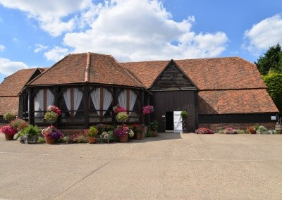 Great Barn ablaze with colourful pots and hanging baskets.